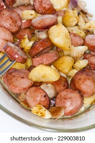 Plate of pieces of sausage, potatoes, garlic and meat with a piece of sausage on a fork punctured over white background