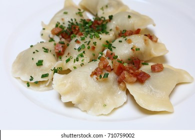 Plate of pierogi or varenyky stuffed filled dumplings with bacon and green chive onion, traditional East Europe cuisine meal popular in Poland, Ukraine, Slovakia and Russia, close up, high angle view
