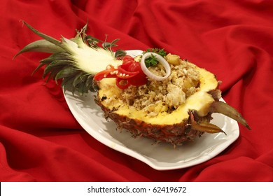 A plate of pineapple fried rice served in a half-cut pineapple