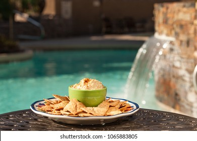 Plate of pita chips and bowl of fresh hummus by luxury pool with water fall feature in background. Healthy summer snacks by the pool.
