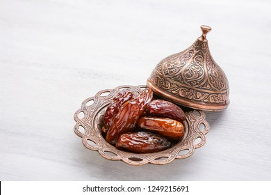 Plate of pitted dates on a white wooden background.