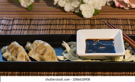Plate of pork and vegetable Chinese potsticker dumplings with ginger soy dipping sauce