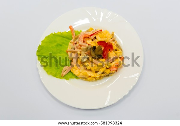 A plate with a portion of salad with ham, mushrooms, peppers, corn and mayonnaise. The recipe for a delicious dish from the chef.