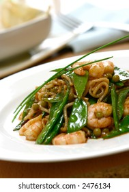 A plate of prawn noodles with sugarsnap peas and peas , garnish with chives.