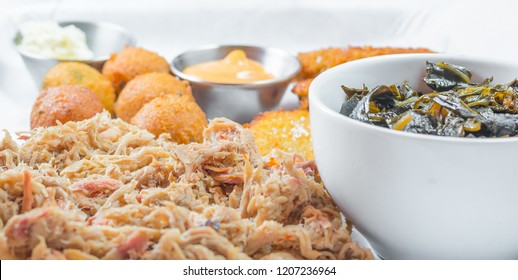 A plate of pulled pork barbecue with collard greens, hushpuppies,  and fired green tomatoes