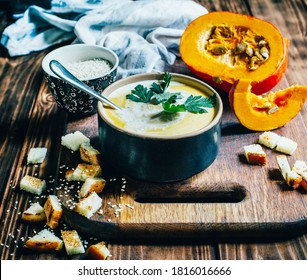 a plate of pumpkin soup on a background of pumpkin and bread crumbs on a dark wooden table