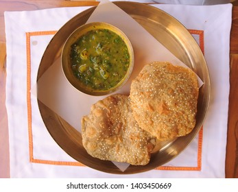 A plate of puri and sabzi a traditional Indian meal on a white napkin