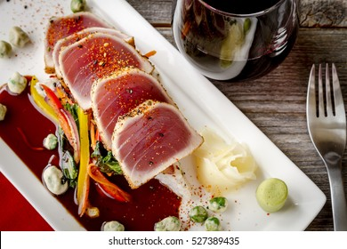 Plate of rare seared Ahi tuna slices with bok choy stir fry vegetables and wasabi peas and glass of red wine from above