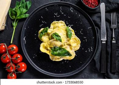 Plate of ravioli with Parmesan and Basil. Black background. Top view