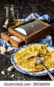 A plate of ravioli pasta and vintage grater on the dark table