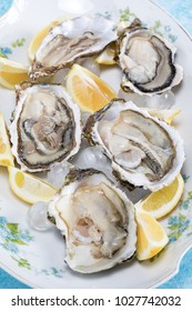 Plate with raw oysters and lemon slices on ice.
