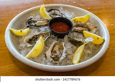 Plate of raw oysters on the half shell on a bed of ice with lemon wedges and cocktail sauce.