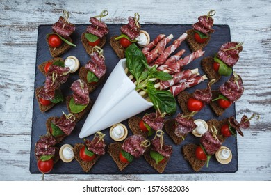 Plate with raw salami and cherry tomatoes.
