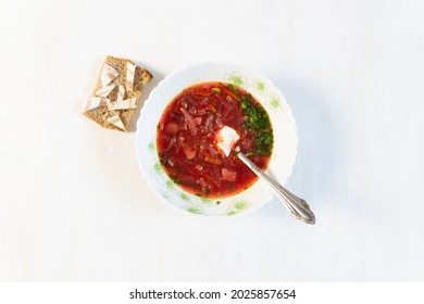 Plate of red soup borshc with spoon, sour cream, on white table with bread and salo