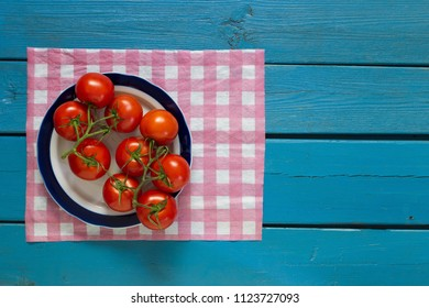 A plate with red tomatoes is on a checkered napkin on a blue wooden background, the top view