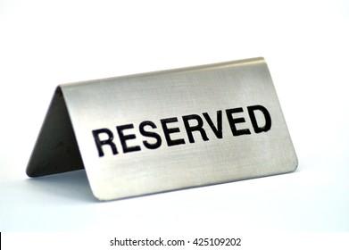 Plate of reservation of table of aluminum restaurant on white bottom.