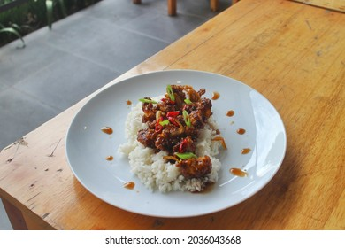 a plate of rice and chicken blackpepper sauce at a restaurant in the city