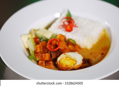 A plate of rice with a side dish of balado potato, a piece of egg. simple and inexpensive food