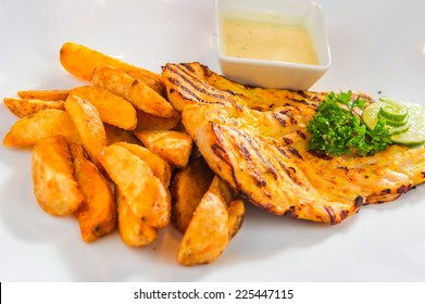 Plate of roasted chicken fillet with french fries and sauce.
