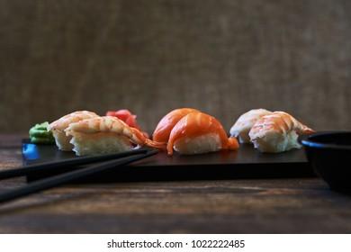 Plate of rolls. Sushi set sashimi and sushi rolls served on wooden plate. Sushi rolls with salmon, eel, tuna, avocado, royal prawn, cream cheese  caviar tobica, chuka. Sushi menu. Japanese food.