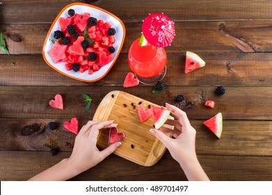 Plate with salad of watermelon, blackberries, mint. hand cut hearts of watermelon on a wooden board. Watermelon fresh in a glass with an umbrella. On a wooden background.