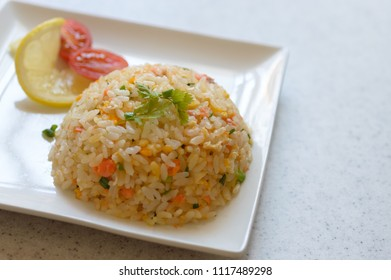 a plate of salmon fried rice with the assortment of vegetables
