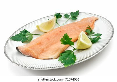 plate with salmon trout fillet, parsley and lemon isolated on white with clipping path