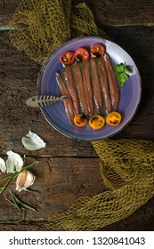 Plate of salted anchovies with olive oil, tomatoes and garlic on an old wooden table, still life. Vertical image.