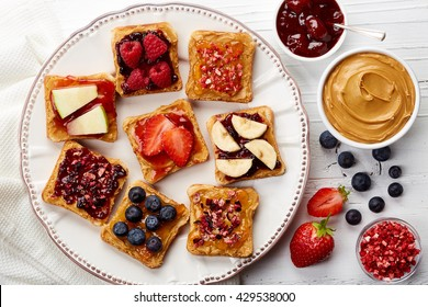 Plate of sandwiches with peanut butter, jam and fresh fruits on white wooden background from top view
