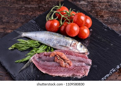 Plate with sardines cherry tomatoes and aromatic herbs on a table