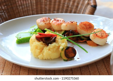 Plate of scallops cooked with its vegetables garnish in a french gastronomic