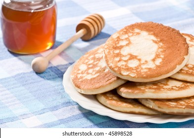 Plate of Scotch pancakes ready to eat with honey jar and dipper in background