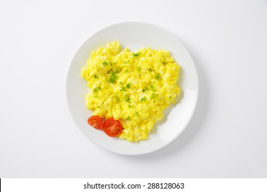 plate of scrambled eggs on white background