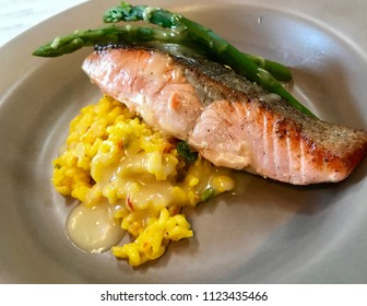 Plate of seared salmon with asparagus and yellow wild rice