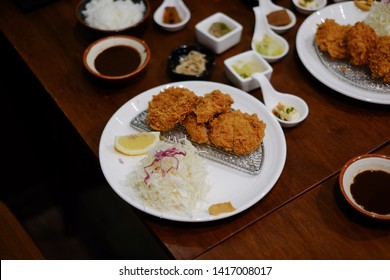 A plate serving pieces of crispy fried tenderloin pork or tonkatsu with sliced of fresh cabbage , lemon and seasoning sauce. Japanese traditional food.