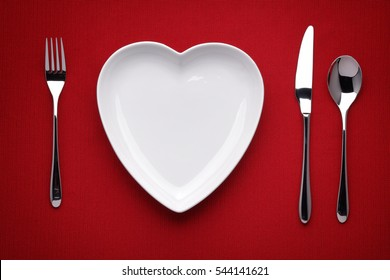plate in shape of heart, table knife and fork on red