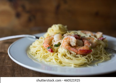 A plate of shrimp scampi and angel hair pasta. Shown on rustic wooden background.