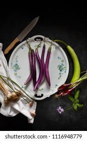 Plate with sicilian agricultural products: eggplant Perlina variety, garlic, spring red onions and a particular squash called cucuzza or zucchetta serpent.