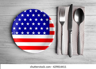Plate with silver cutlery on wooden background. American cuisine food concept