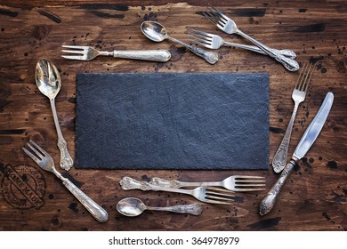 Plate of slate on a wooden background with cutlery
