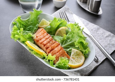 Plate with slice of delicious salmon on table