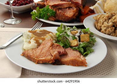 A plate of sliced baked ham and mashed potatoes