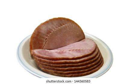 Plate of sliced ham on white background