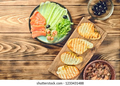 Plate with sliced pieces of red salmon fish, cucumber slices, arugula olives and rolls and fried bread baguette cooking canapes bruschetta homemade recipes on wooden table