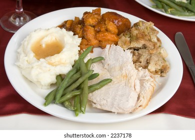 A plate of sliced turkey, stuffing, mashed potatoes and gravy, candied yams and fresh green beans.