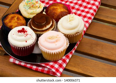 plate of small homemade cupcakes served on wooden table