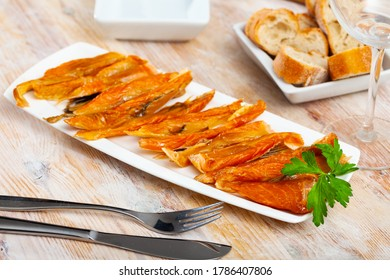 Plate with smoked salmon bellies garnished with fresh greens on wooden background