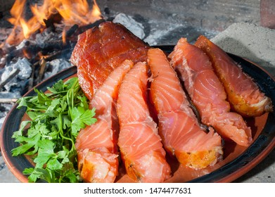 The plate of smoked salmon on the charcoal grill with the burning charcoal in the background