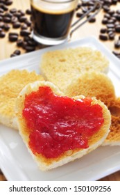 a plate with some heart-shaped toasts with strawberry jam with a cup of coffee and coffee beans in the background
