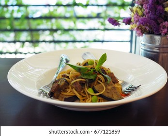 A plate of spaghetti with grilled eggplant (aubergine), roasted mushroom and Edamame decorated with basil on wooden table. Vegan or vegetarian Food concept. Selective